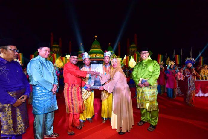 Bupati Karimun Aunur Rafiq menyerahkan piala bergilir juara umum kepada Camat Moro, Rina pada malam penutupan MTQ Kabupaten Karimun ke XI, di Coastal Area, Sabtu malam (30/3/2019).