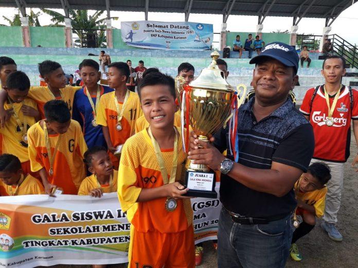 Kabid SMP Dinas Pendidikan Kab Karimun, Sugito menyerahkan piala pada juara I SMP1 Kuba